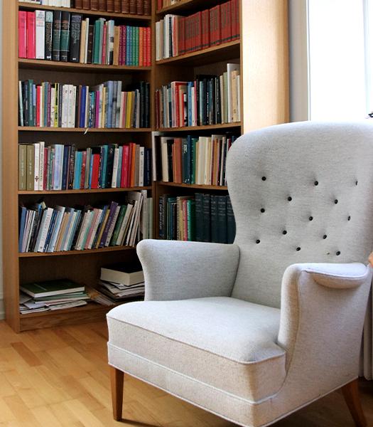 Reol med bøger og lænestol