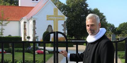 Præst smiler ved låget til kirkegård