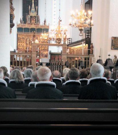 Præster sidder i en kirke