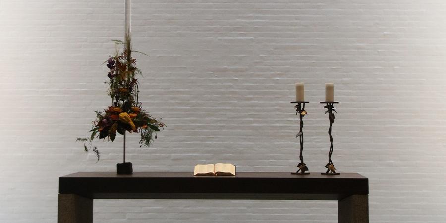 Alter med blomst, lysestager og bible